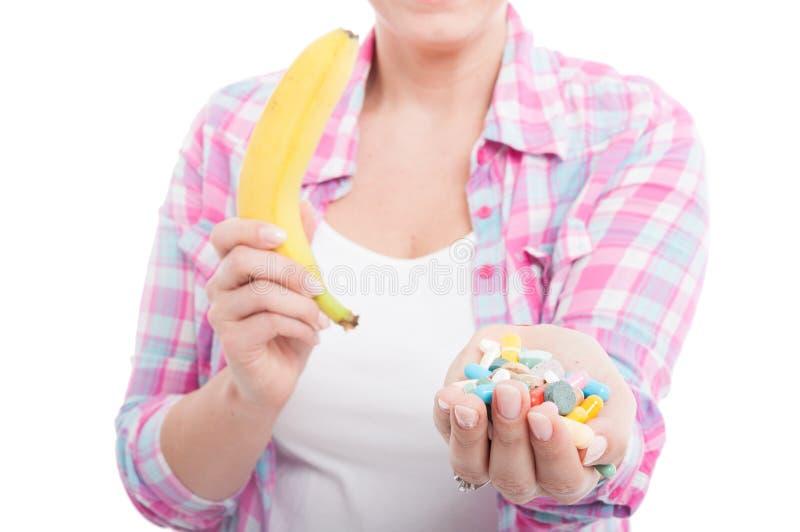 Pillole della banana e della compressa della tenuta della donna fotografie stock libere da diritti