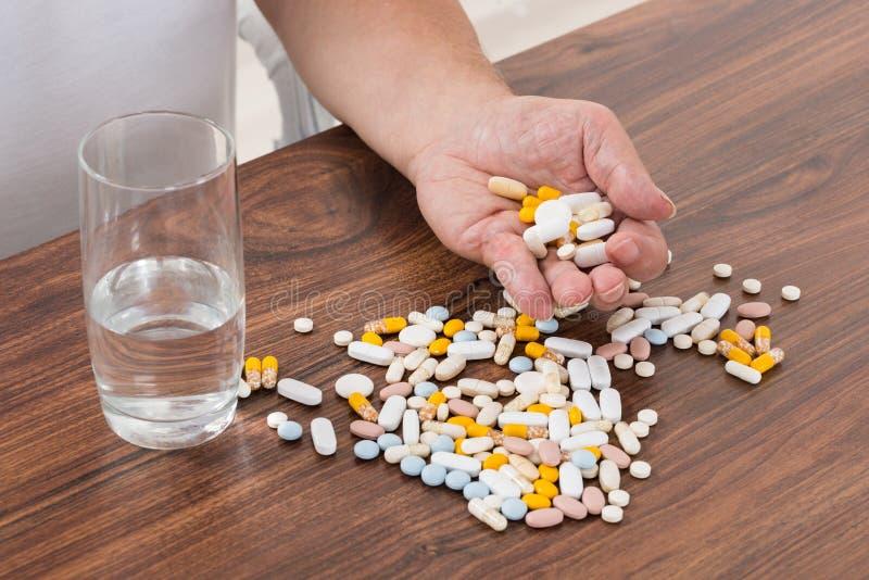 Pillole della tenuta della mano del ` s della persona immagine stock
