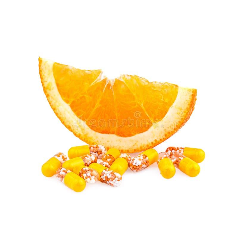 Pillole della vitamina e frutta arancio fotografia stock libera da diritti