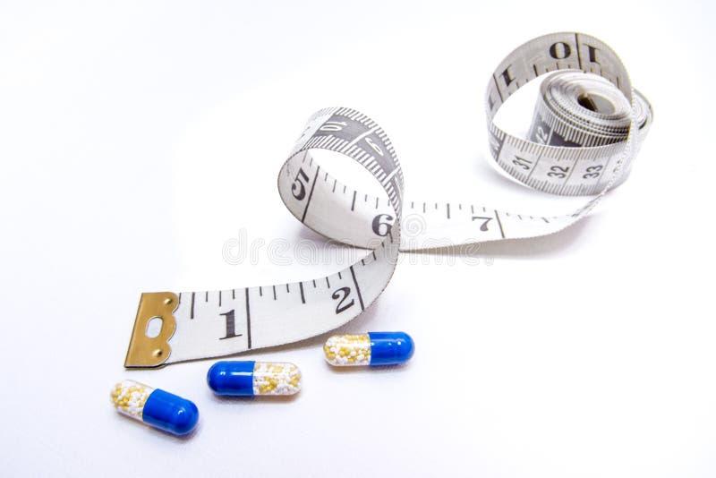 Pillole di dieta con nastro adesivo di misurazione fotografie stock libere da diritti