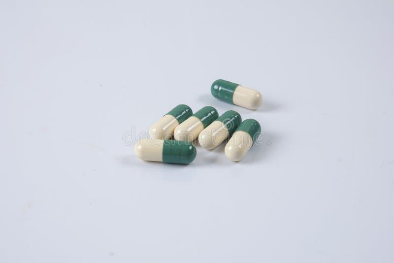 Pillole di verde/gialle medicina su bianco Sanità concettuale fotografie stock libere da diritti