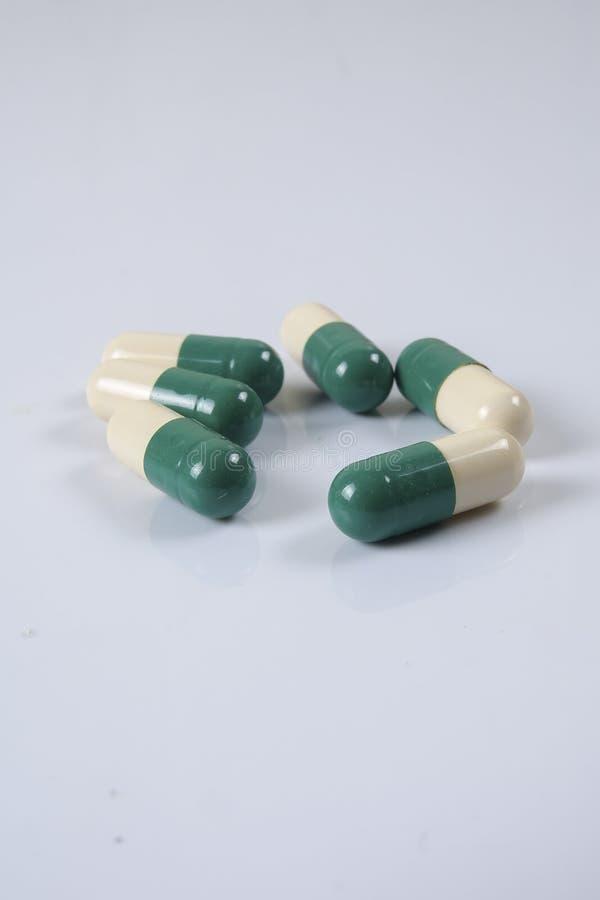 Pillole di verde/gialle medicina su bianco Sanità concettuale fotografia stock
