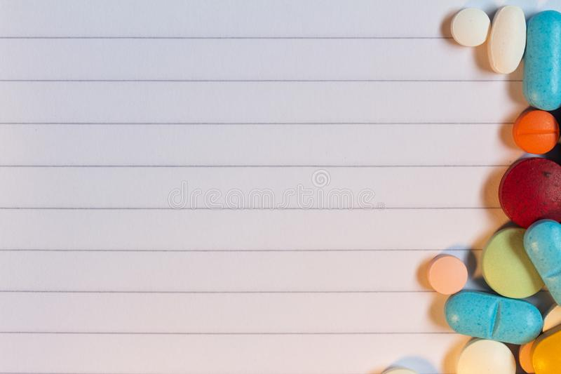 Pillole e capsule colorate su un fondo a strisce neutrale fotografia stock