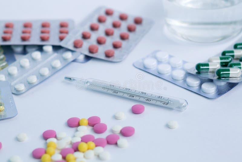 Pillole e compresse con thermometr su fondo bianco fotografia stock