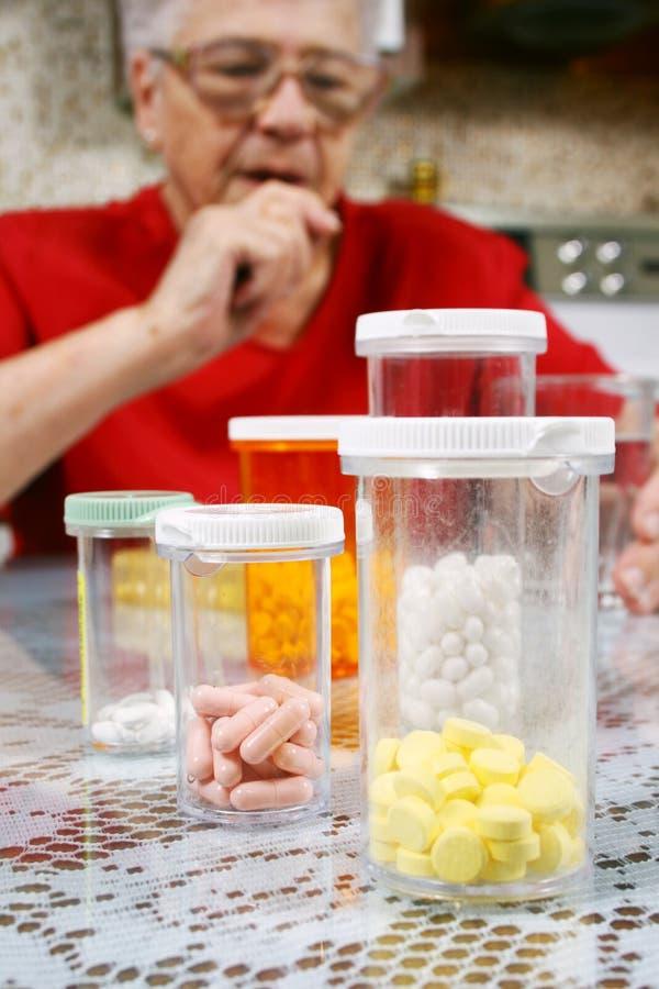Pillole e donna maggiore immagini stock libere da diritti
