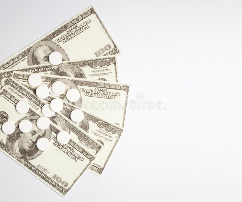 Pillole e soldi bianchi, concetto di spese sanitarie, costo di cura, immagini stock libere da diritti