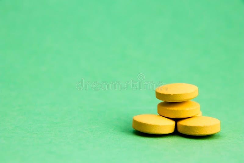 Pillole gialle isolate su fondo verde con il percorso di ritaglio Concetto della farmacia e della medicina fotografia stock libera da diritti