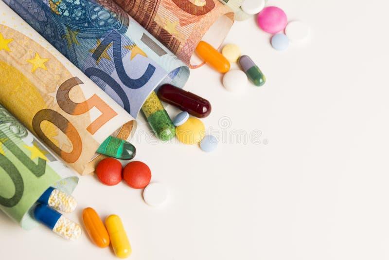 Pillole mediche colorate dalle euro banconote acciambellate, soldi dal concetto dell'industria farmaceutica fotografia stock libera da diritti