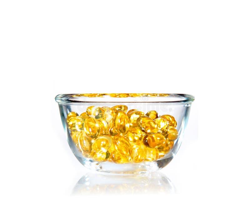 Pillole molli gialle luminose del gel in ciotola di vetro trasparente fotografie stock libere da diritti