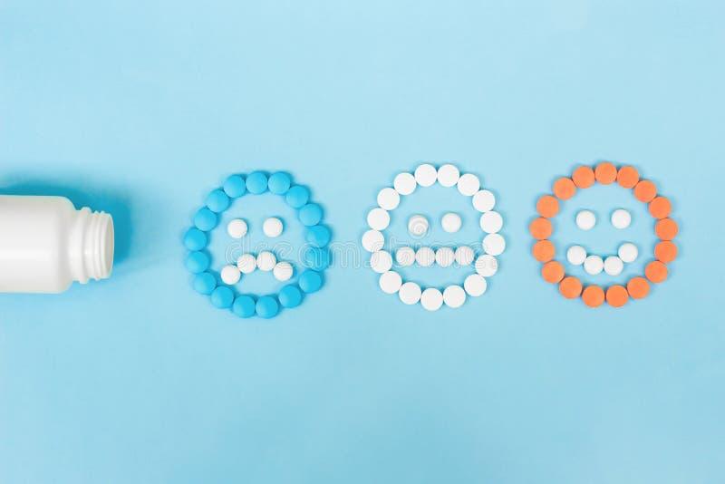 Pillole multicolori e fronti divertenti e una bottiglia di plastica su un fondo blu Il concetto degli antidepressivi e di guarigi fotografie stock