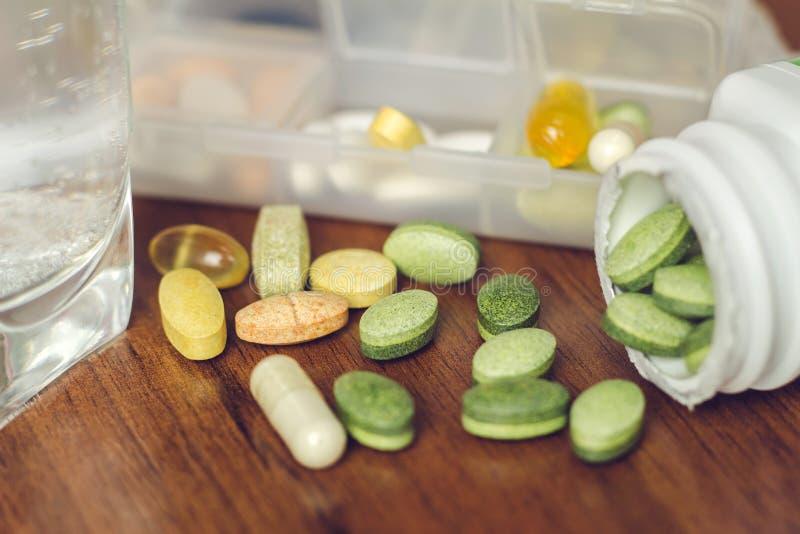 Pillole naturali miste della vitamina e dell'integratore alimentare sulla tavola di legno e nella bottiglia immagine stock libera da diritti