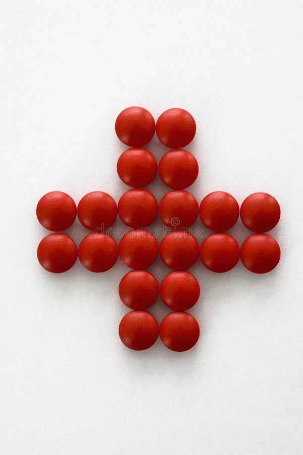 Pillole nel modulo della croce rossa fotografia stock
