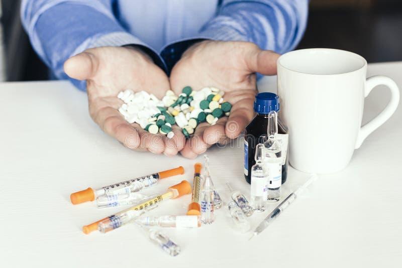Pillole o capsule della medicina con le mani dei man's su fondo bianco con lo spazio della copia immagini stock