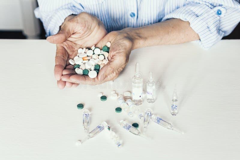 Pillole o capsule della medicina con le vecchie mani dei woman's su fondo bianco con lo spazio della copia immagini stock libere da diritti