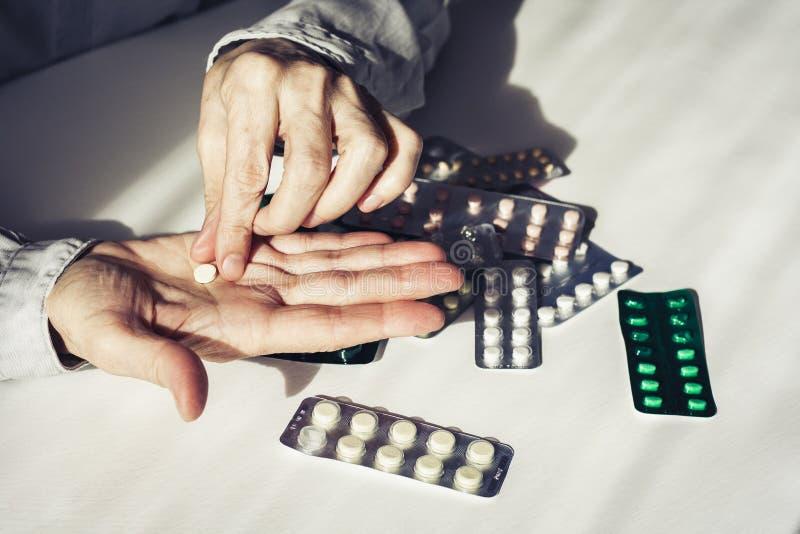 Pillole o capsule della medicina con le vecchie mani dei woman's su fondo bianco con lo spazio della copia Blister fotografia stock libera da diritti