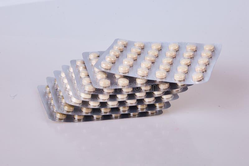 Pillole o compresse di erbe della medicina in bolle d'argento su fondo bianco fotografia stock libera da diritti