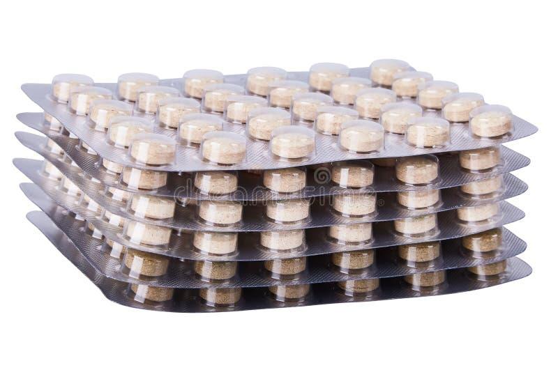 Pillole o compresse di erbe della medicina in bolle d'argento su fondo bianco fotografia stock