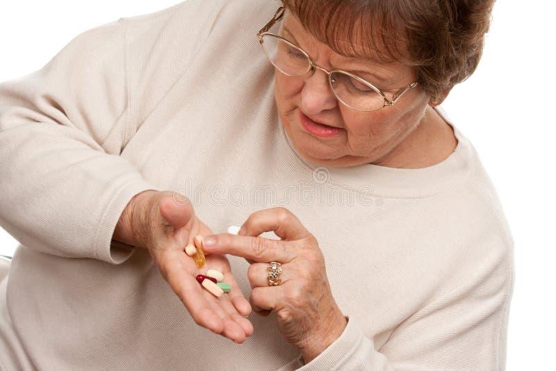 Pillole senior attraenti del farmaco e della donna fotografia stock libera da diritti