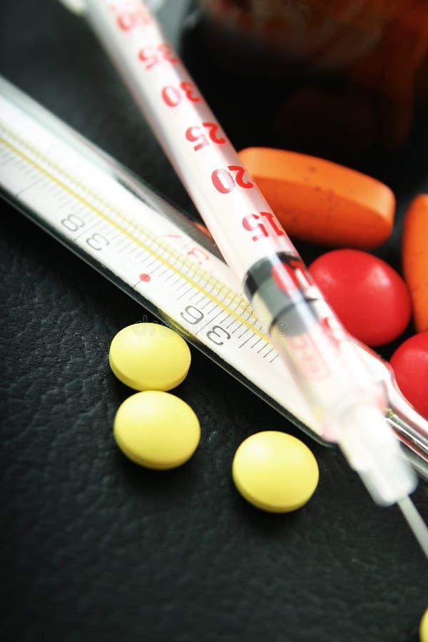 Pillole, siringa e termometro