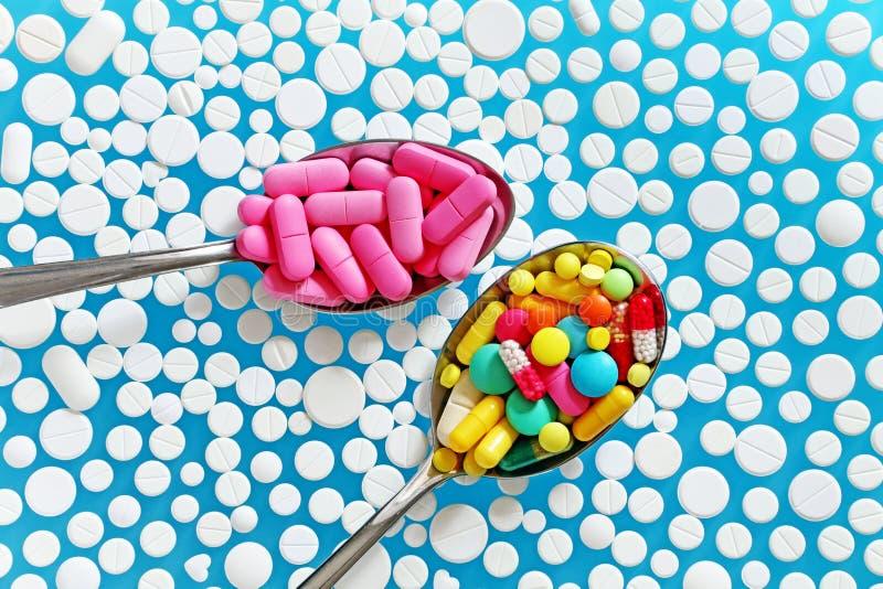 Pillole variopinte in cucchiai su un fondo blu fotografia stock