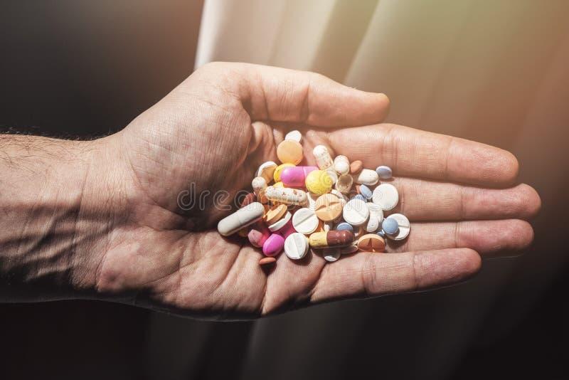 Pillole variopinte e medicine nella mano immagine stock libera da diritti