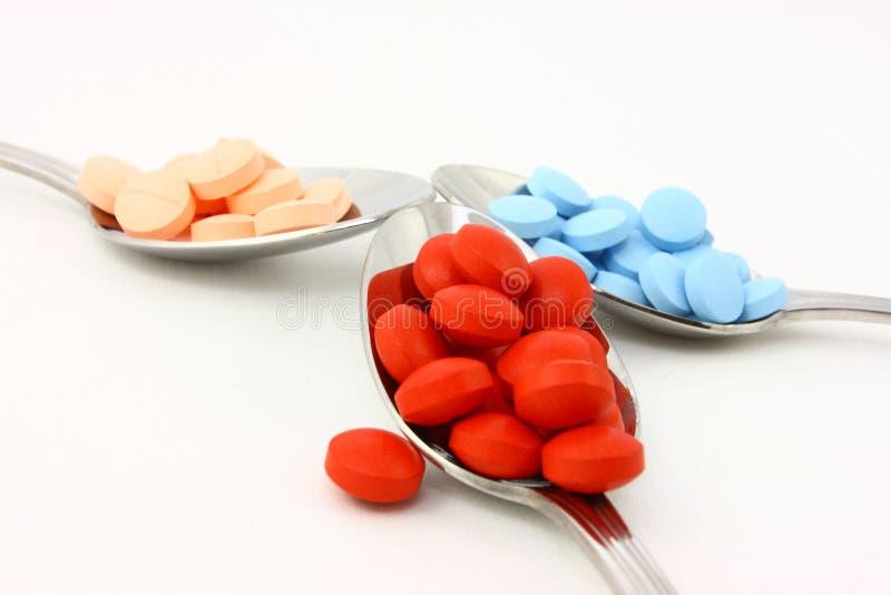 Pillole variopinte in tre cucchiai immagini stock