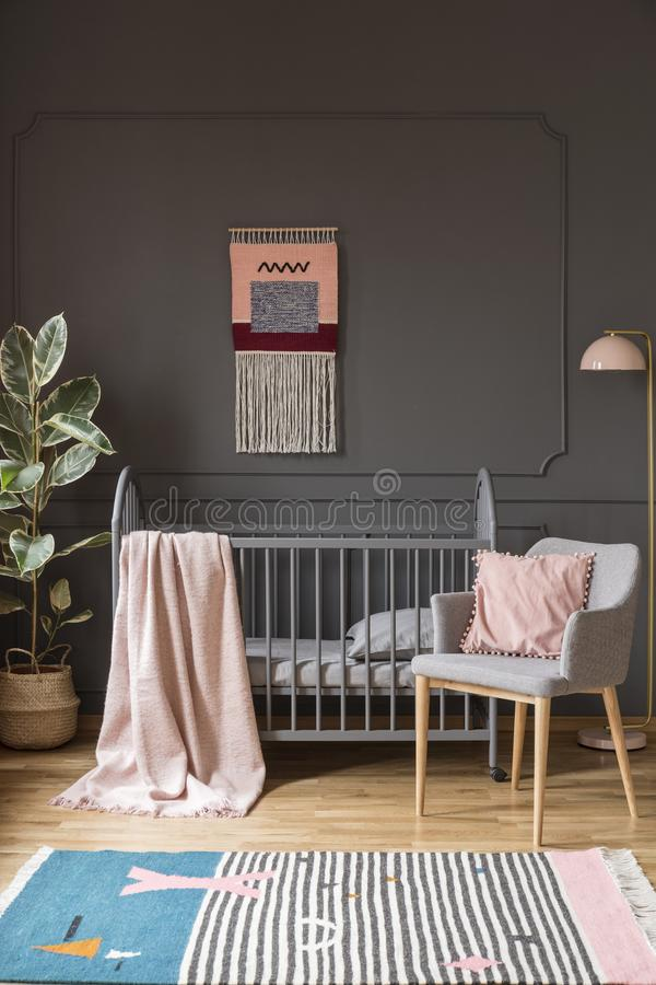 Pillow auf grauem Lehnsessel nahe bei Bett mit Decke in Kind-` s bedr lizenzfreie stockfotos