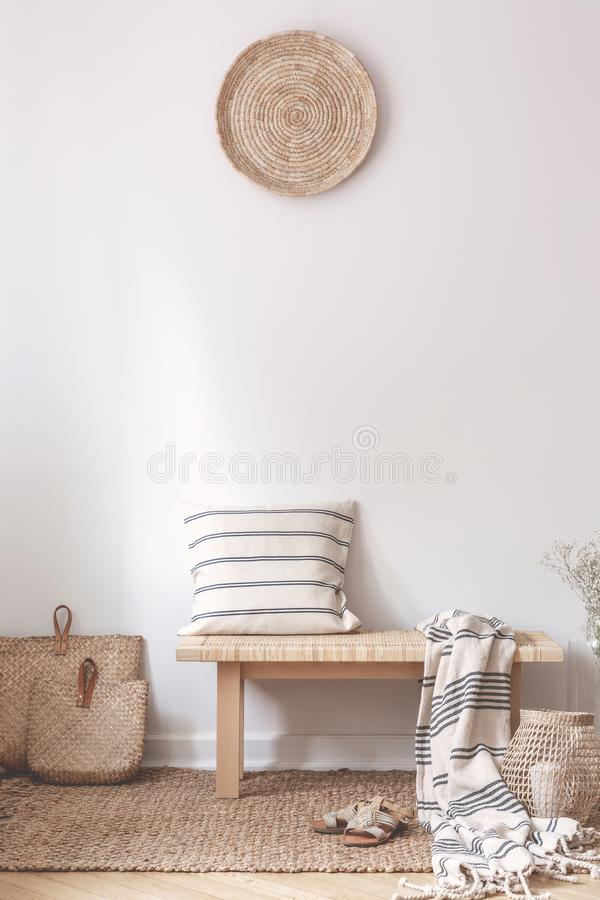 Pillow and blanket on wooden stool in white living room interior with brown plate. Real photo. Concept stock image