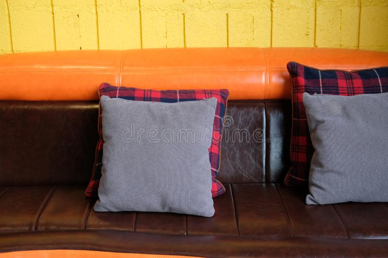 Pillow on brown orange leather sofa couch beside yellow wall. Blue pillow on brown orange leather sofa couch beside yellow wall royalty free stock photos