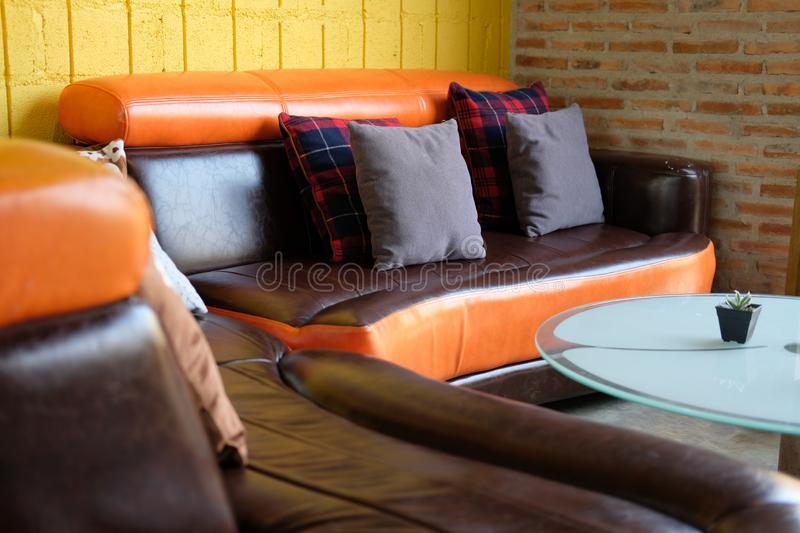 Pillow on brown orange leather sofa couch beside yellow wall. Blue pillow on brown orange leather sofa couch beside yellow wall royalty free stock image