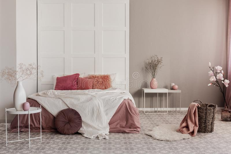 Amaranth pillow and orange bedding on king size bed in fashionable bedroom interior. Pillow and dirty orange bedding on king size bed in fashionable bedroom stock images