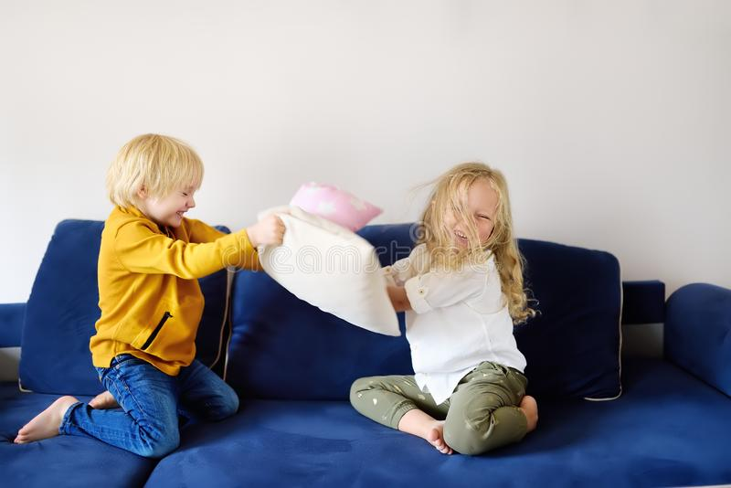 Pillow fight. Brother and sister play together. Active games for siblings at home stock photos