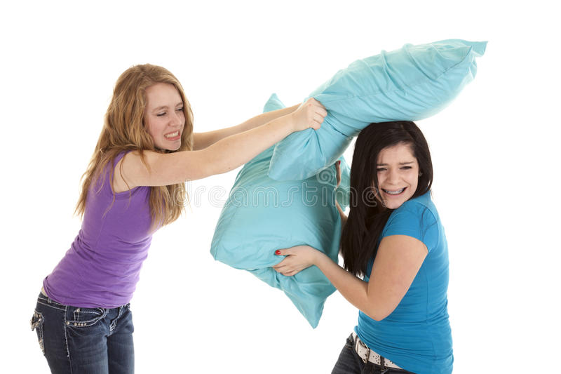 Pillow fight girls. A couple of teenage girls having a pillow fight, laughing and having some fun stock photos