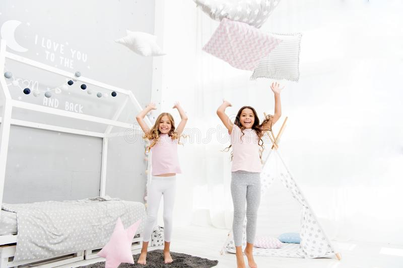 Pillow fight pajama party. Evening time for fun. Sleepover party ideas. Girls happy best friends or siblings in cute stock image