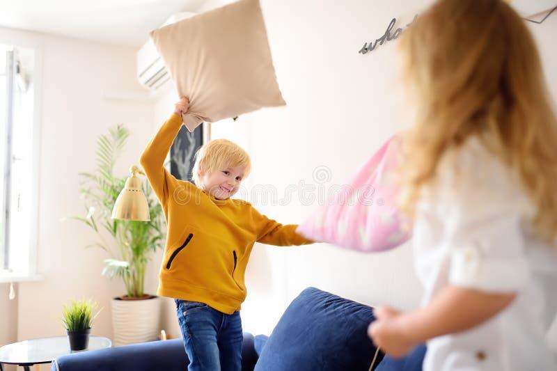 Pillow-strid Broder och syster leker tillsammans Aktiva spel för syskon hemma royaltyfria bilder