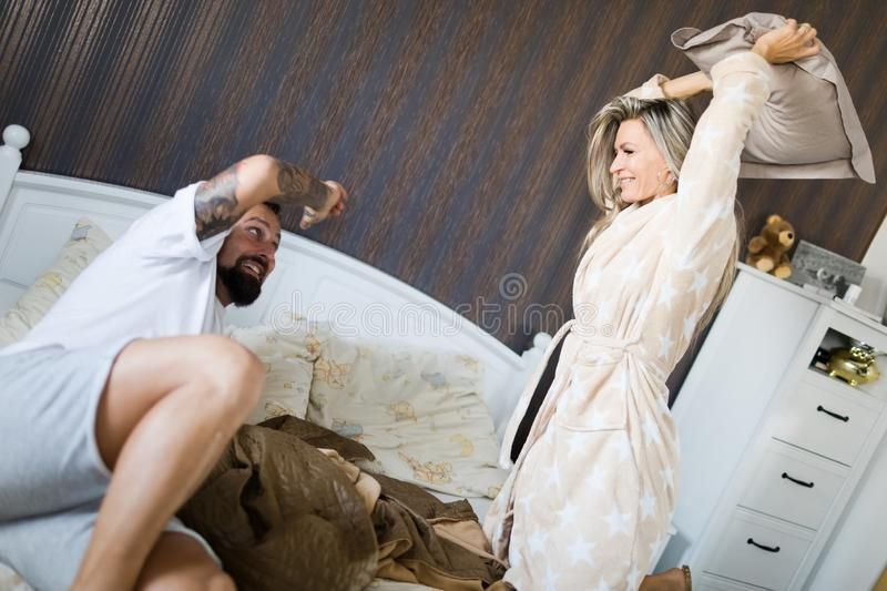 Pillow war of husband and wife in bedroom royalty free stock photo