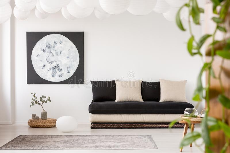 Pillows on black sofa in white living room interior. With moon poster and grey carpet. Real photo royalty free stock photo