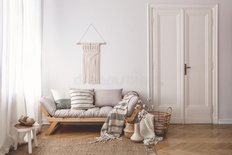 Pillows and blanket on wooden sofa in white loft interior with door and table on carpet. Real photo. Concept stock photo
