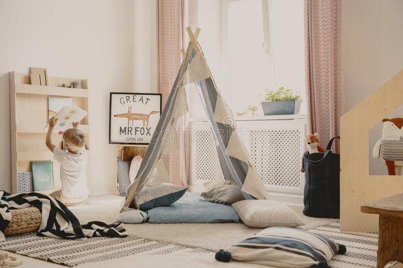 Pillows and carpets on the floor of cozy playroom of single kid, real photo. Pillows and carpets on the floor of cozy playroom of single kid,  photo stock photo