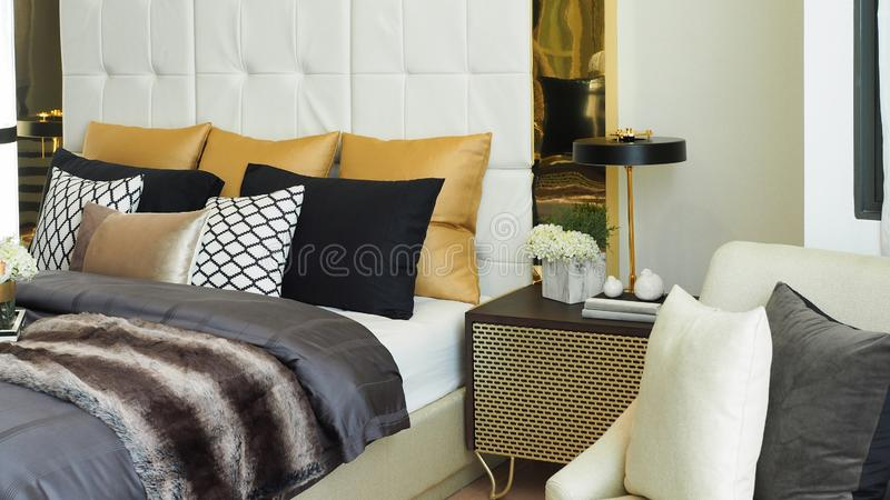 Pillows and cushions in white, beige brown and black color tone on bed and bedside table with lamp in modern luxury bedroom royalty free stock photo