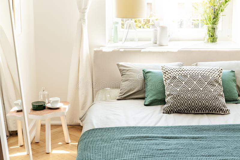 Pillows and green sheets on bed in bedroom interior with white t. Able next to mirror. Real photo concept royalty free stock photography
