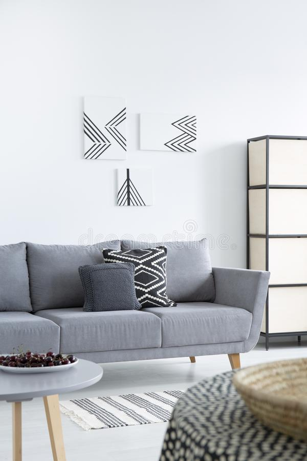 Pillows on grey sofa in patterned living room interior with posters and cherries on table. Real photo stock photo