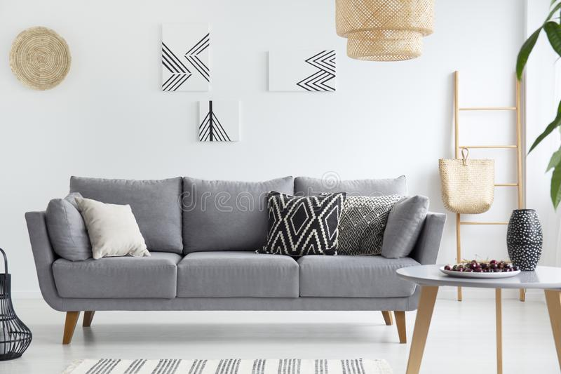 Pillows on grey sofa in white living room interior with posters, lamp and wooden table. Real photo. Concept stock photography