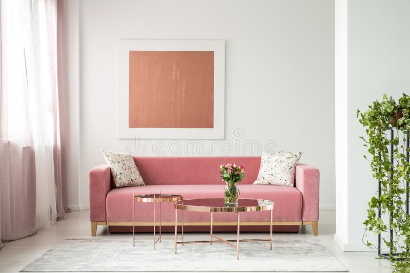 Pillows on pink sofa in white apartment interior with painting and flowers on copper table. Real photo. Concept stock photography