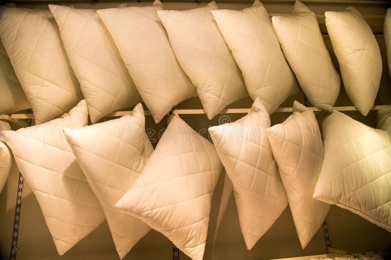 Pillows of white color suspended on a crossbeam in rows. Household items, light industry stock image