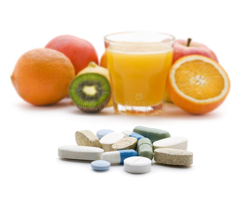 Pills. With fresh fruit in background isolated royalty free stock images