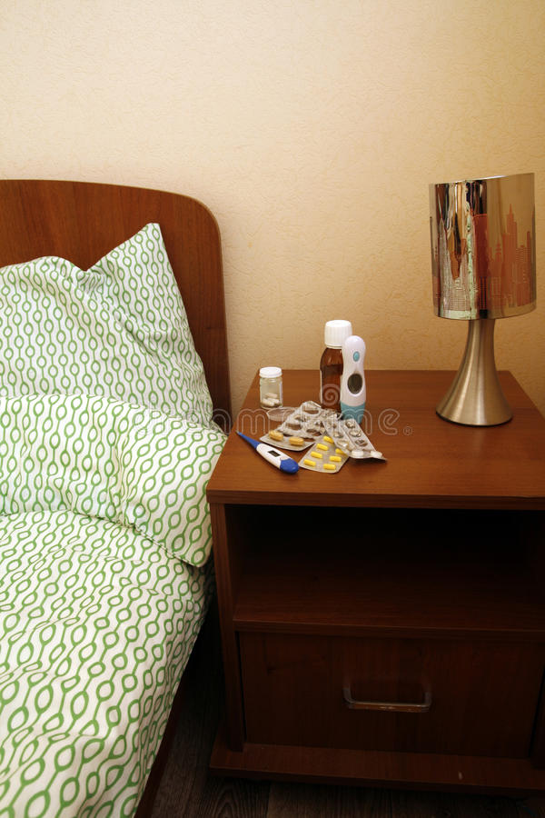 Pills on a bedside table. Medicine bottles and blister strips with pills on the bedside table near the bed royalty free stock photo