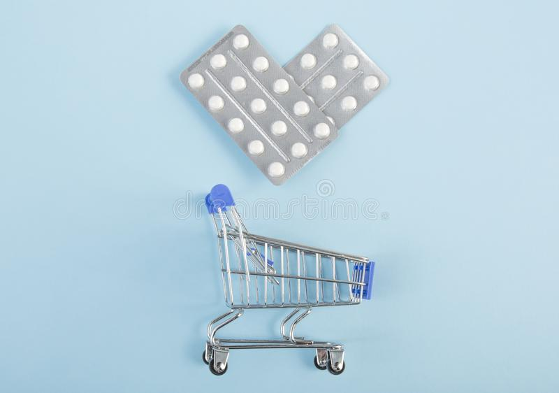 Pills in a blister pack in the shape of a heart with shopping cart on blue background. stock photography