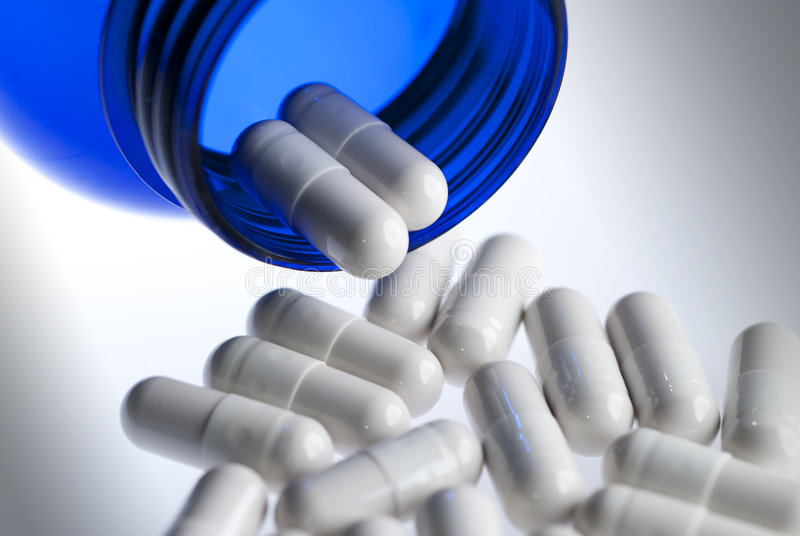 Pills in blue bottle horizontal. White capsules pouring out of a blue bottle on neutral background stock images