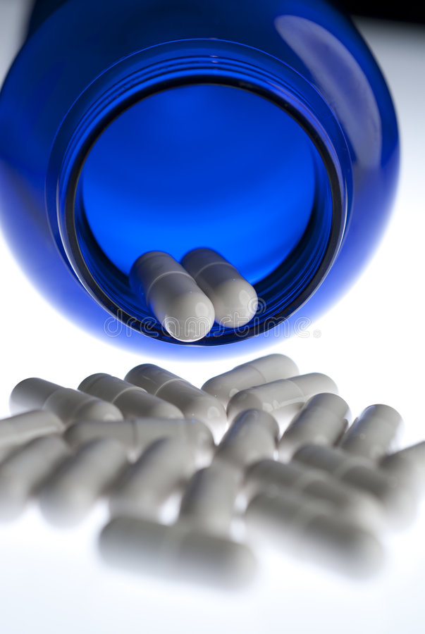 Pills in blue bottle vertical. White capsules pouring out of a blue bottle on neutral background with very limited depth of field royalty free stock images